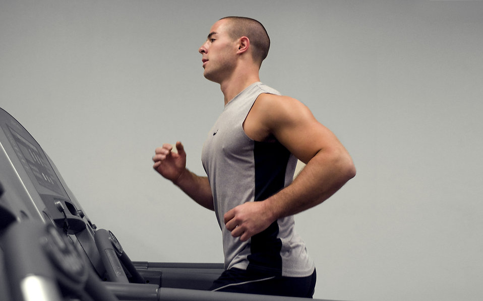A healthy young man running on a treadmill in a gym : Free Stock Photo