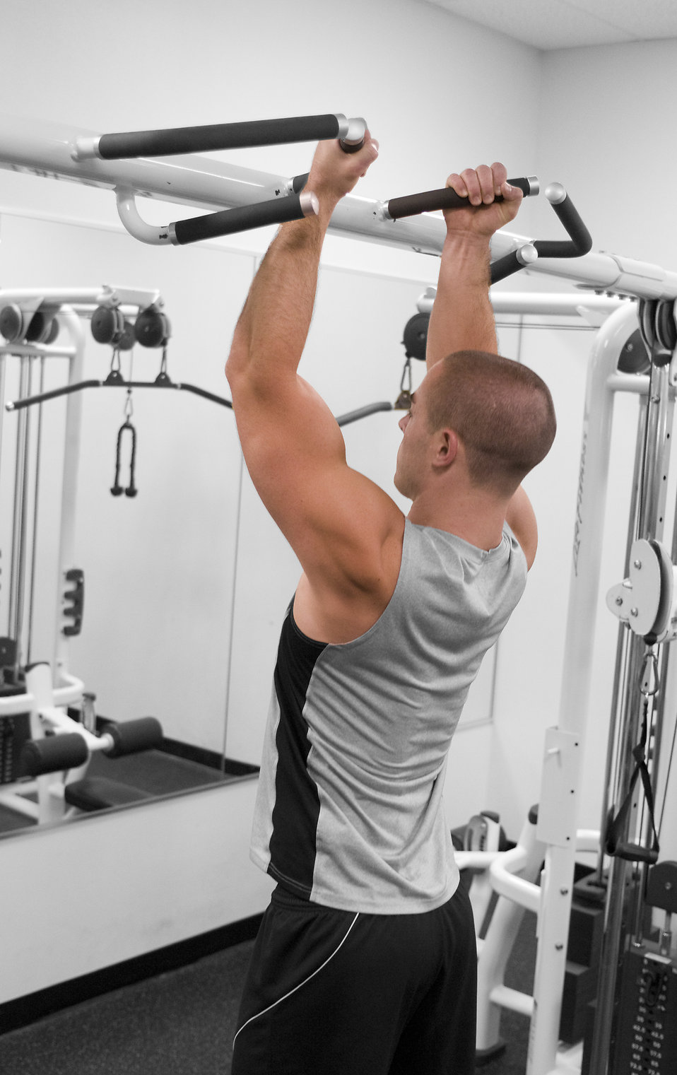 A healthy young man performing pull-ups in a gym : Free Stock Photo