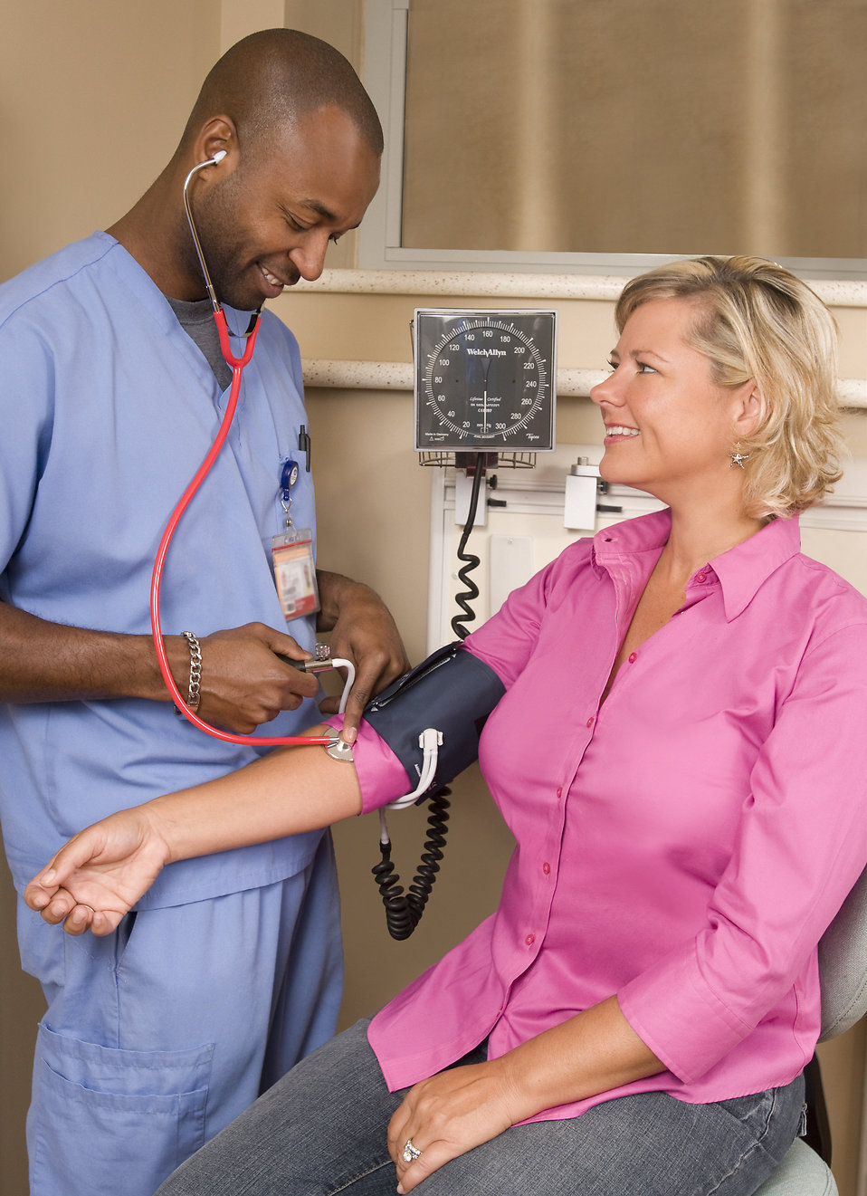 A male nurse taking a woman's blood pressure : Free Stock Photo