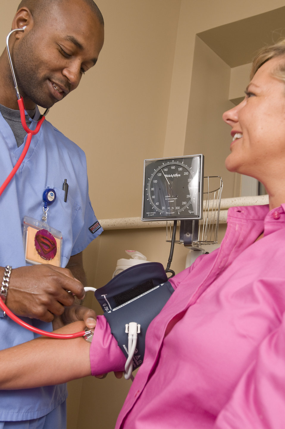 A male nurse taking the blood pressure of a woman : Free Stock Photo