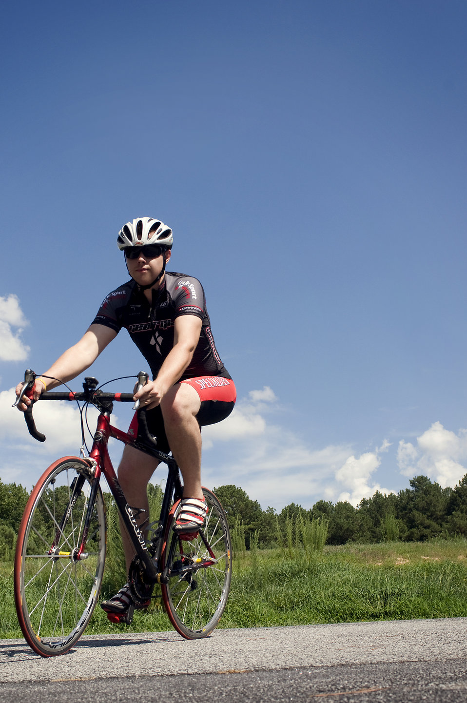 This photograph depicts a male bicyclist, who was riding his bicycle on a sunny Georgia day. As a precaution, he had worn a streamline, aerodynamically-designed helmet, sunglasses, and skin-tight riding wear, all of which would help protect him from the elements, and traumatic injury.