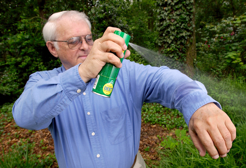 A man spraying insect spray on his shirt : Free Stock Photo