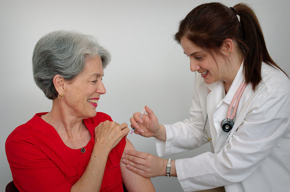 A senior woman receiving a vaccination shot from her doctor : Free Stock Photo