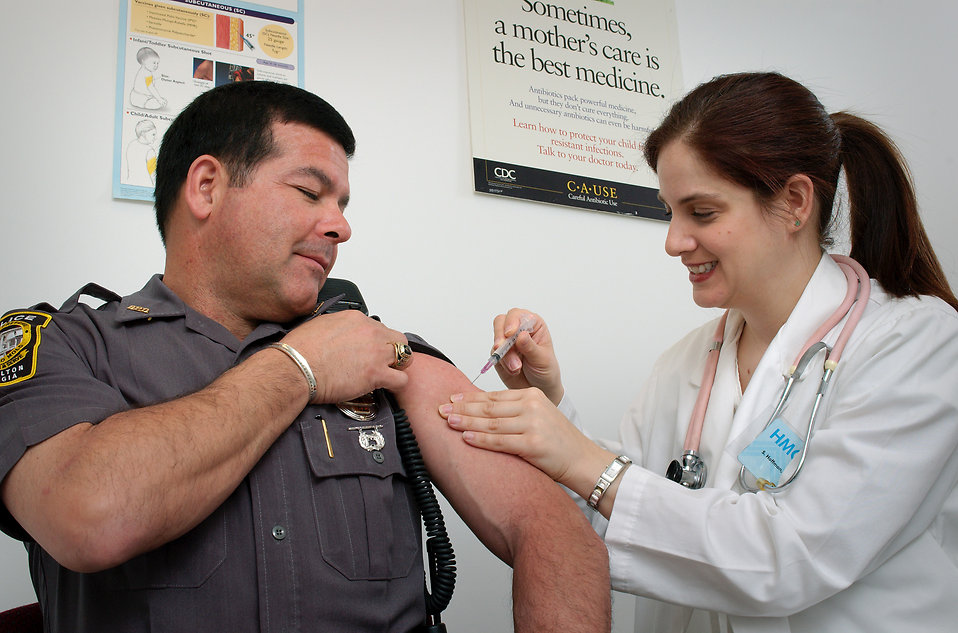 A police officer receiving a vaccination shot from his doctor : Free Stock Photo