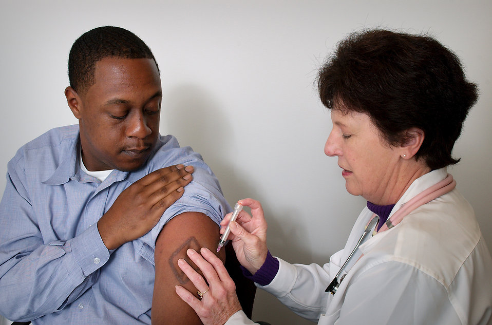 An African-American man receiving a vaccination shot from his doctor : Free Stock Photo