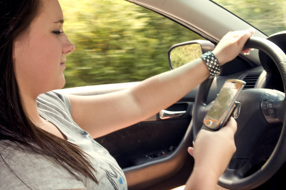 A teen girl texting while driving : Free Stock Photo