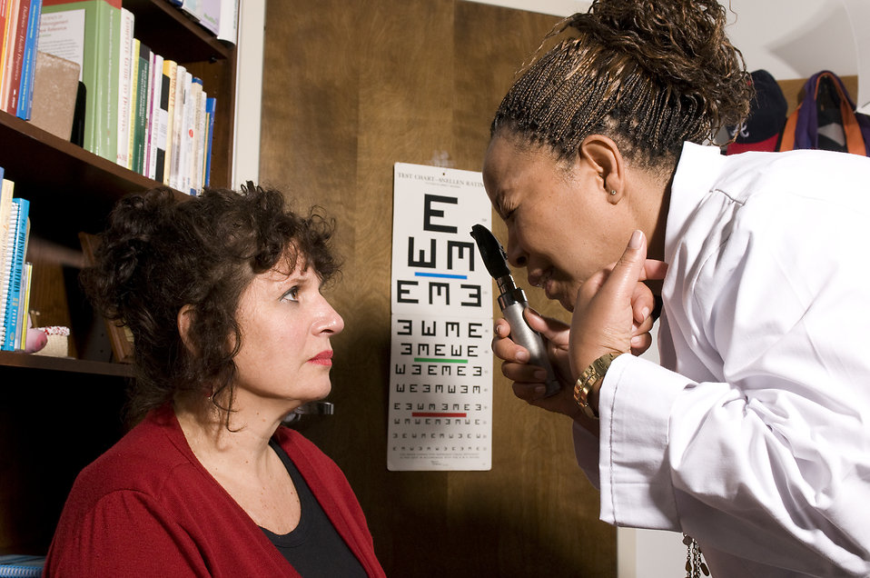 A woman being given an eye exam by her doctor : Free Stock Photo