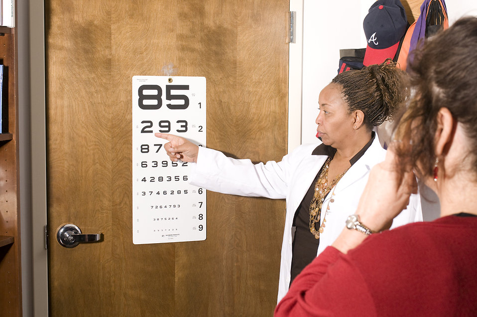 A woman taking an eye exam with her doctor : Free Stock Photo