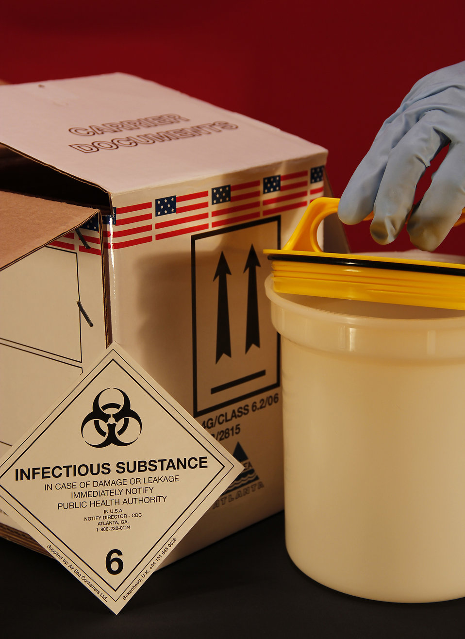 A gloved hand opening a biohazard container : Free Stock Photo