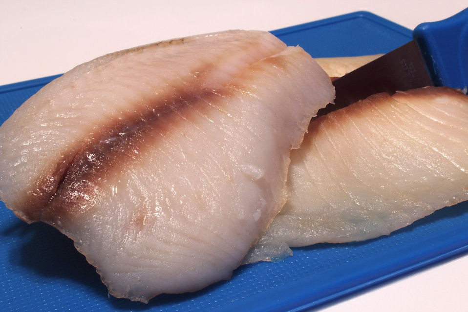 This image depicts two fresh-bought, uncooked fish filets, which were being prepared for a meal, and had been set atop a clean blue silicon cutting-board. The knife used to segment these pieces of fish was shown at right, embedded in one of the filets.