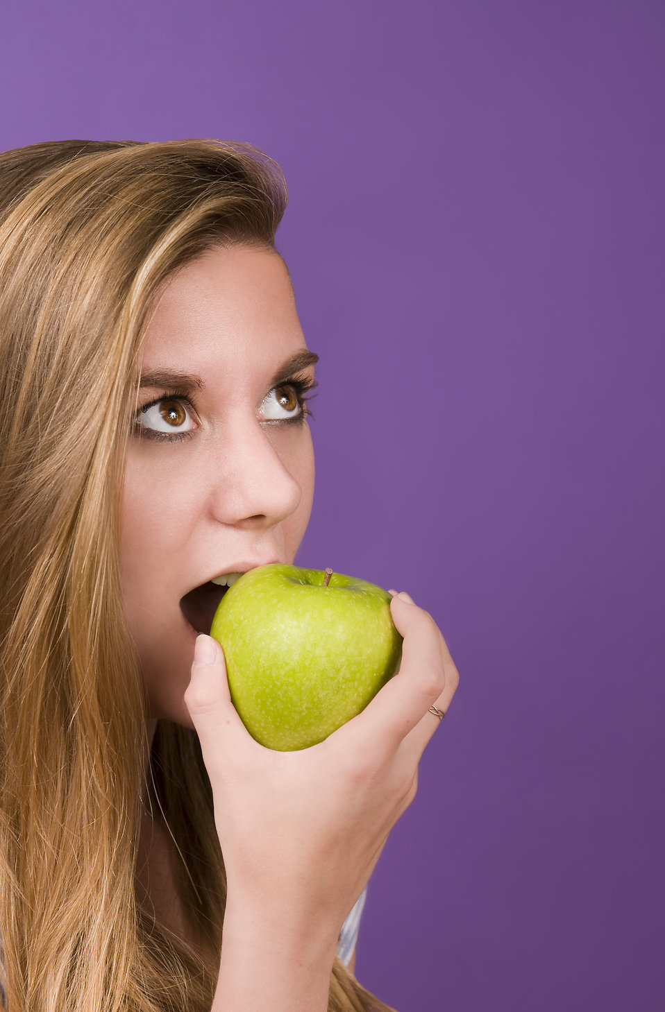 A young woman about to bite into a green apple : Free Stock Photo