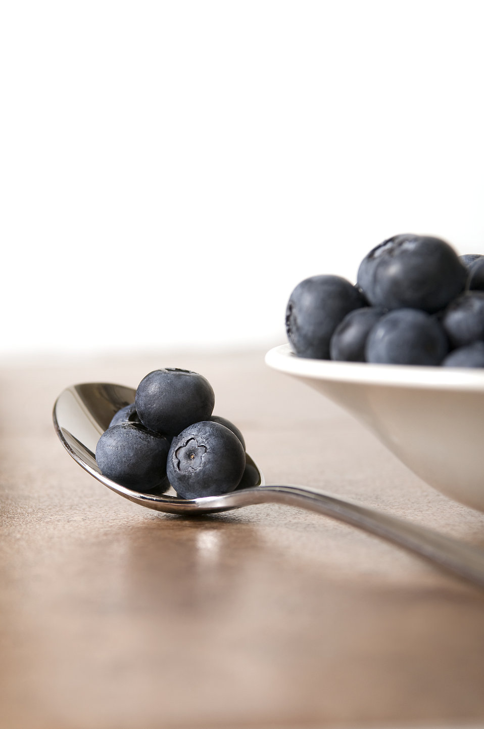 A bowl of and spoonful of blueberries : Free Stock Photo