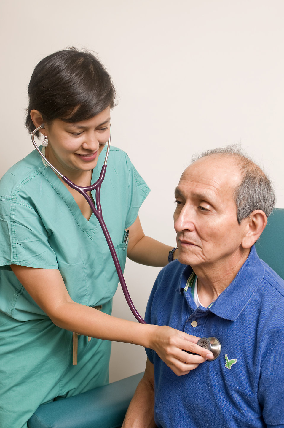 A female doctor examining an elderly male patient : Free Stock Photo