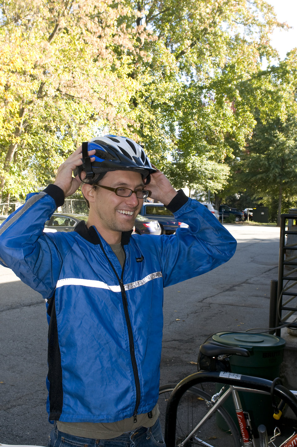 A bicyclist putting on a safety helmet : Free Stock Photo