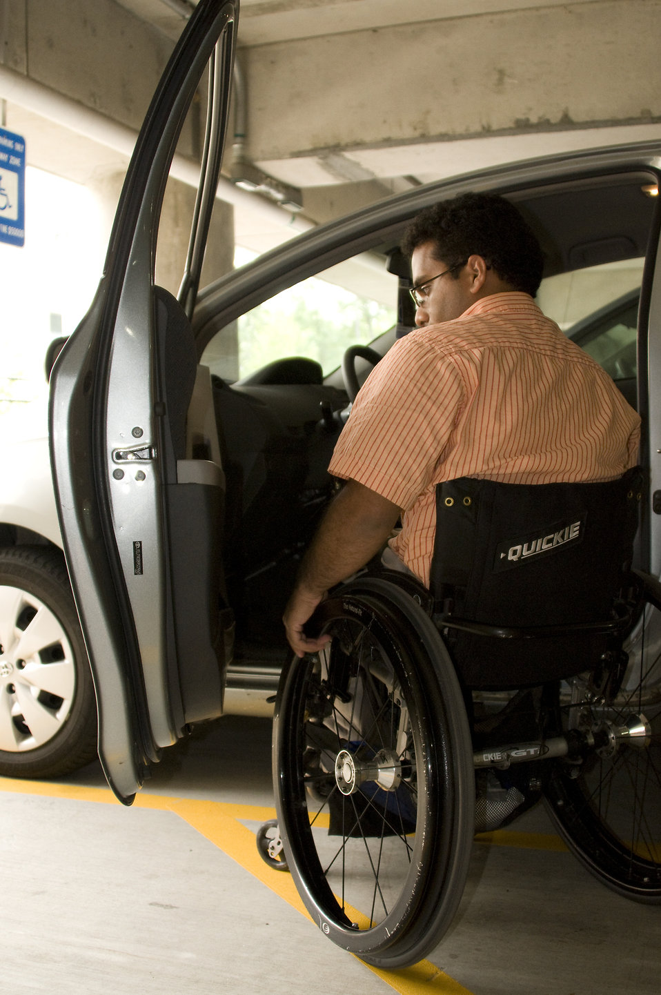 A disabled man in a wheelchair getting out of a car : Free Stock Photo