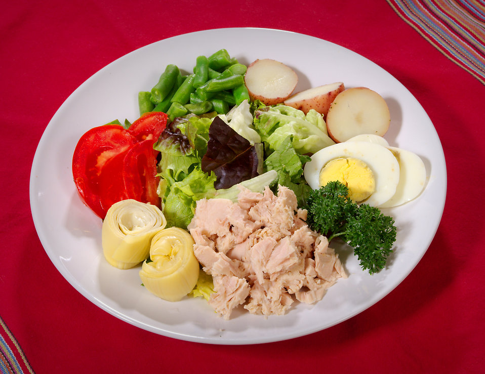 On this plate is a grouping of very healthy foods including a bright red tomato, sliced steamed green beans, leafy spring greens, a hard-boiled egg, sliced red potato, cooked leaks, chopped white meat chicken, and a sprig of parsley. Fresh, light, and nutrient-rich, these foods are loaded with vitamins and minerals, and low in salt, saturated fats, and cholesterol, while being low in calories as well.