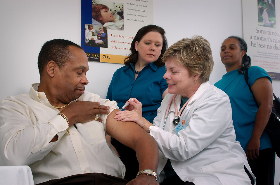 A nurse giving a middle-aged man a vaccination shot : Free Stock Photo