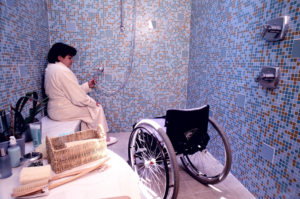 A woman in a wheelchair getting into a shower : Free Stock Photo