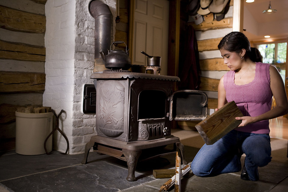 Stove Free Stock Photo A Woman Placing Wood Into A