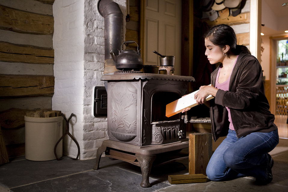 A woman placing wood into a stove : Free Stock Photo