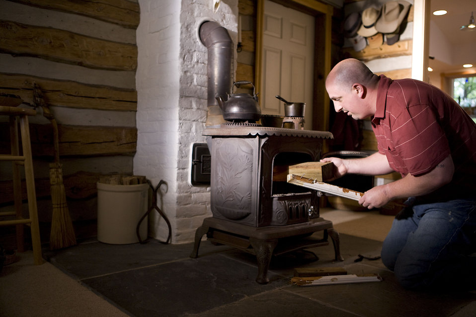 A man placing wood into a stove : Free Stock Photo