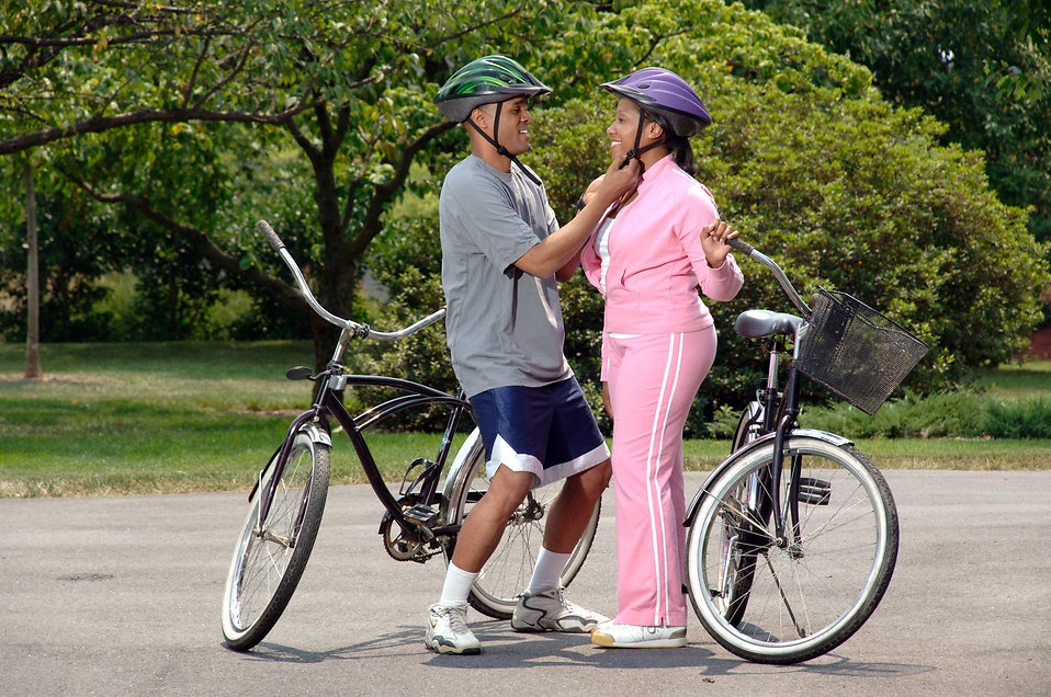 An African-American couple preparing to ride bikes : Free Stock Photo