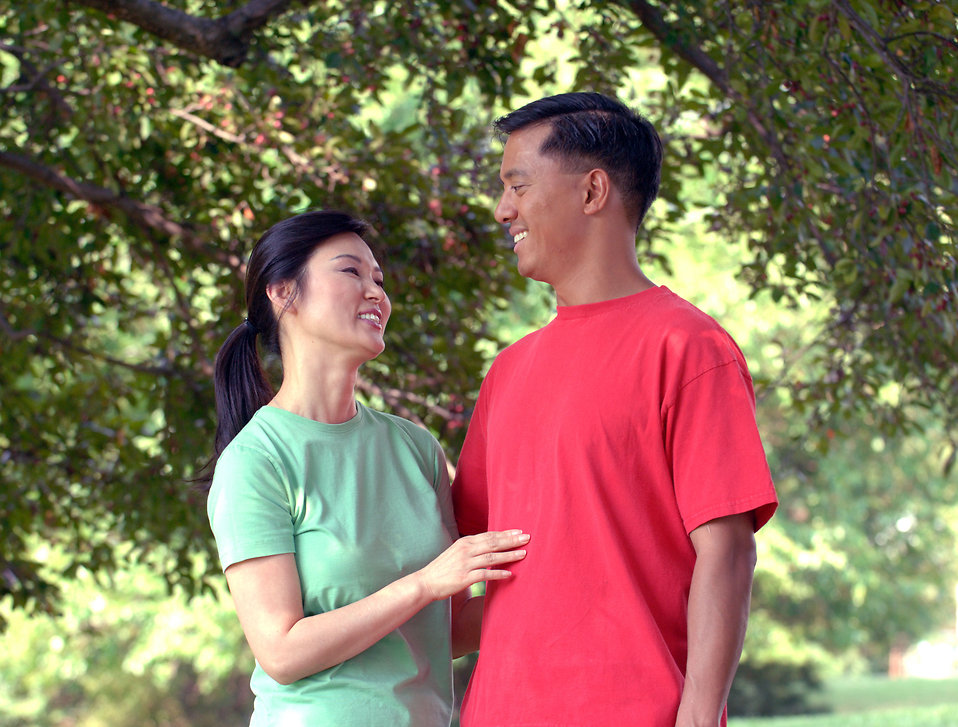 An asian couple smiling at each other outdoors : Free Stock Photo