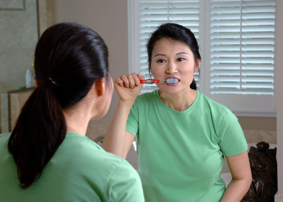 An Asian woman brushing her teeth in a mirror : Free Stock Photo