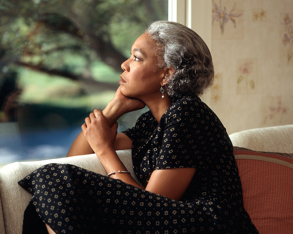 An African-American woman looking out a window : Free Stock Photo
