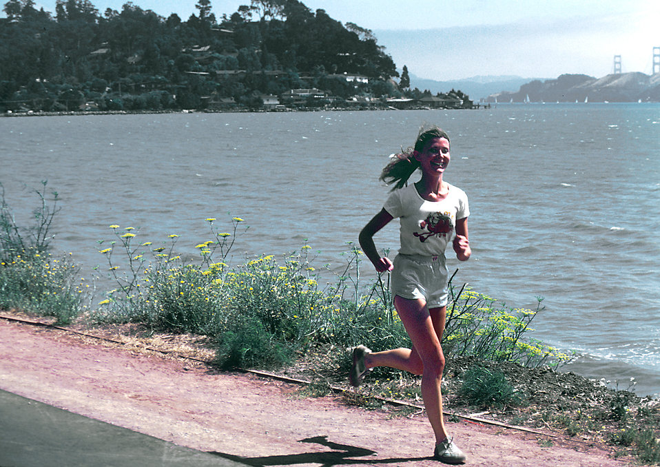 A woman running along a lake shore : Free Stock Photo