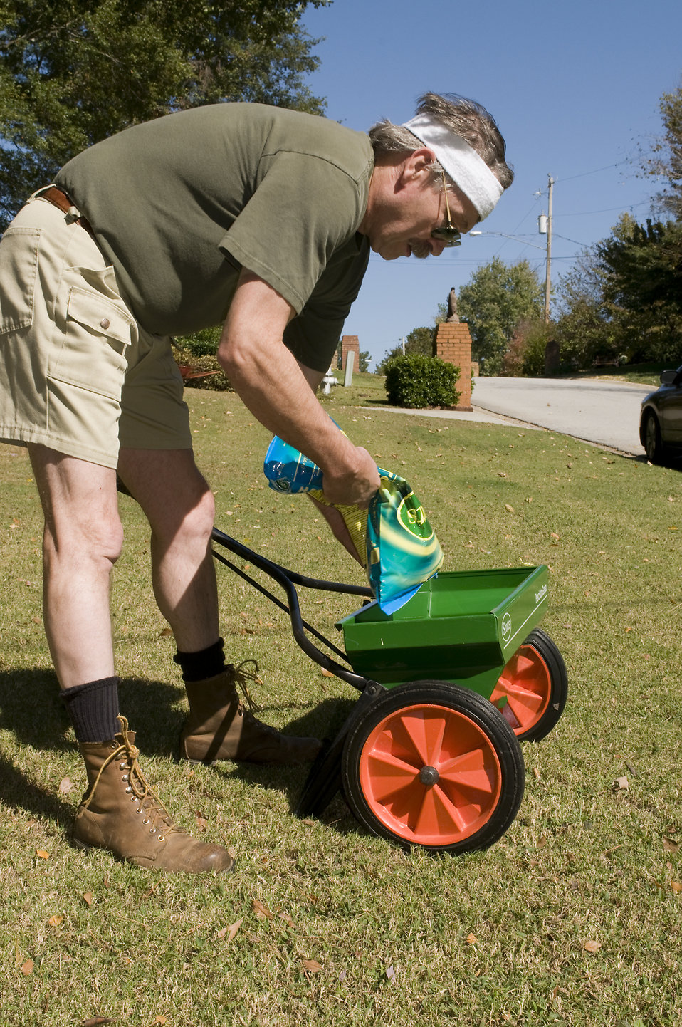 A man fertilizing his lawn with a spreader : Free Stock Photo
