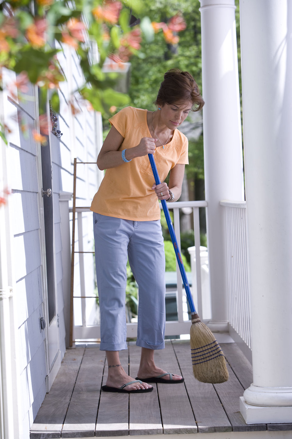 A woman sweeping her front porch : Free Stock Photo