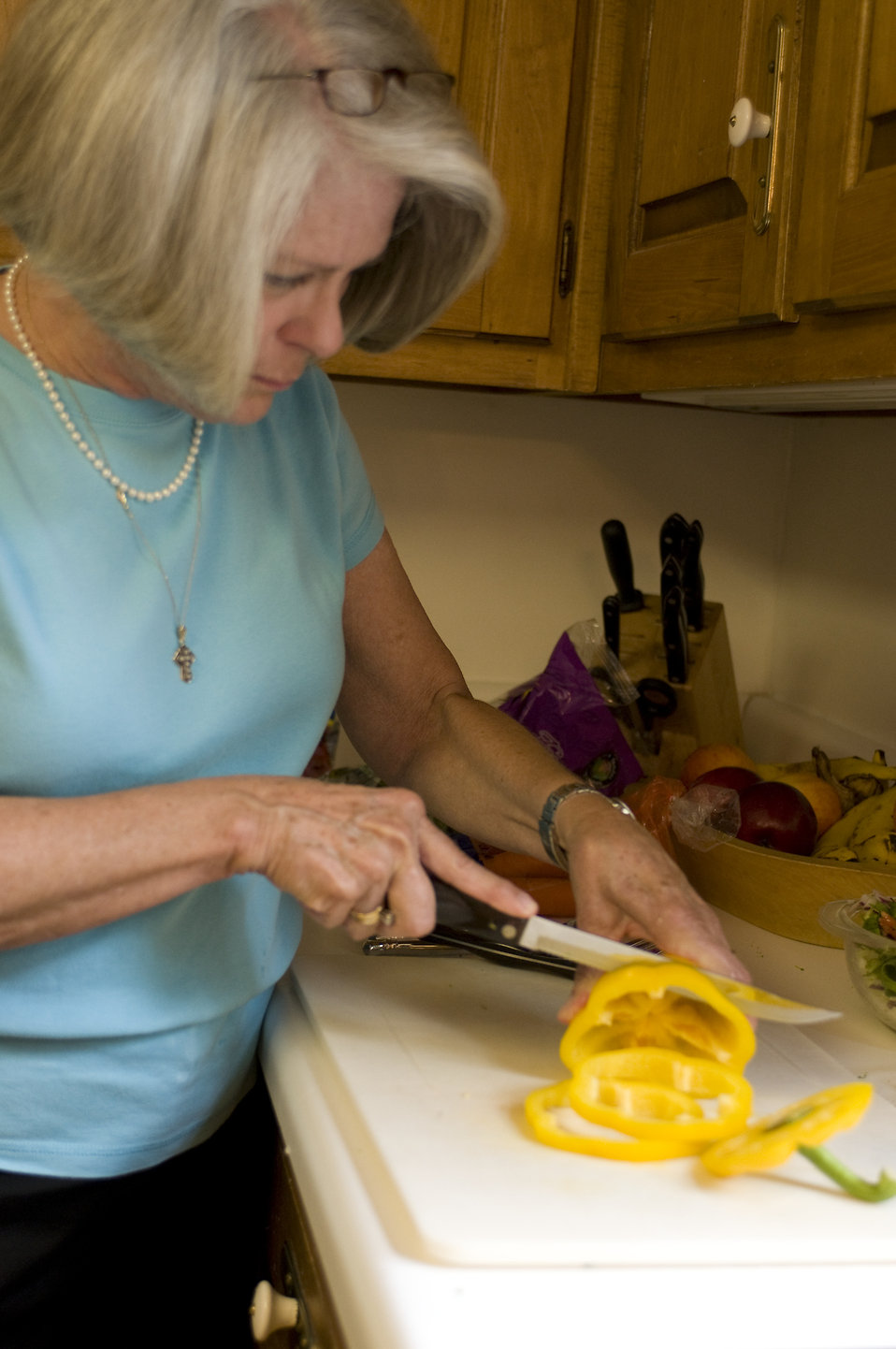 The woman depicted in this image was shown in her kitchen, as she was in the process of preparing a healthy salad, which can be seen in the background, contained in a large glass bowl. At this point in the salad preparation, she was cutting a yellow bell pepper atop a clean white cutting board, the slices of which would then be added to the salad mixture. Note the clean, orderly, uncluttered countertop, which is important to the maintenance of a proper kitchen environment. It is very important to prepare foods in as clean environment as possible, thereby, minimizing the possibility of introducing foodborne contaminants into the food preparation process.