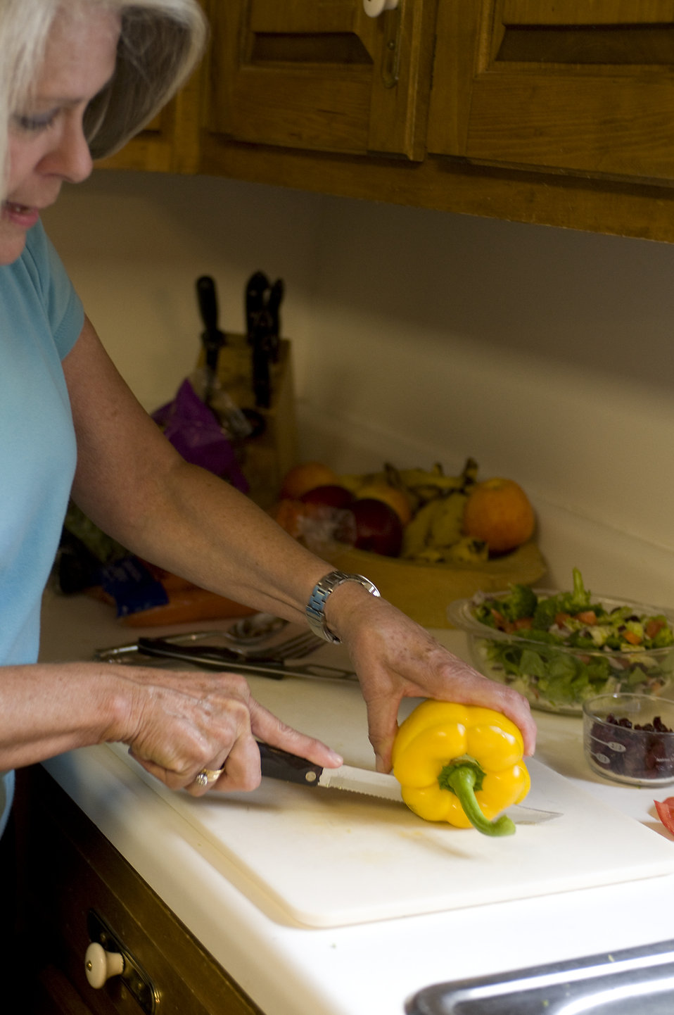 A woman preparing a salad in her kitchen : Free Stock Photo