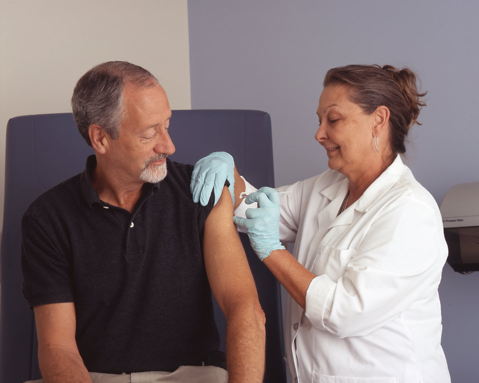 A nurse administering a vaccine to a male patient : Free Stock Photo