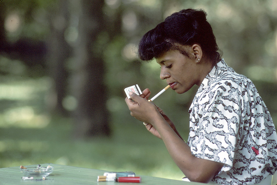 An African American woman lighting a cigarette : Free Stock Photo