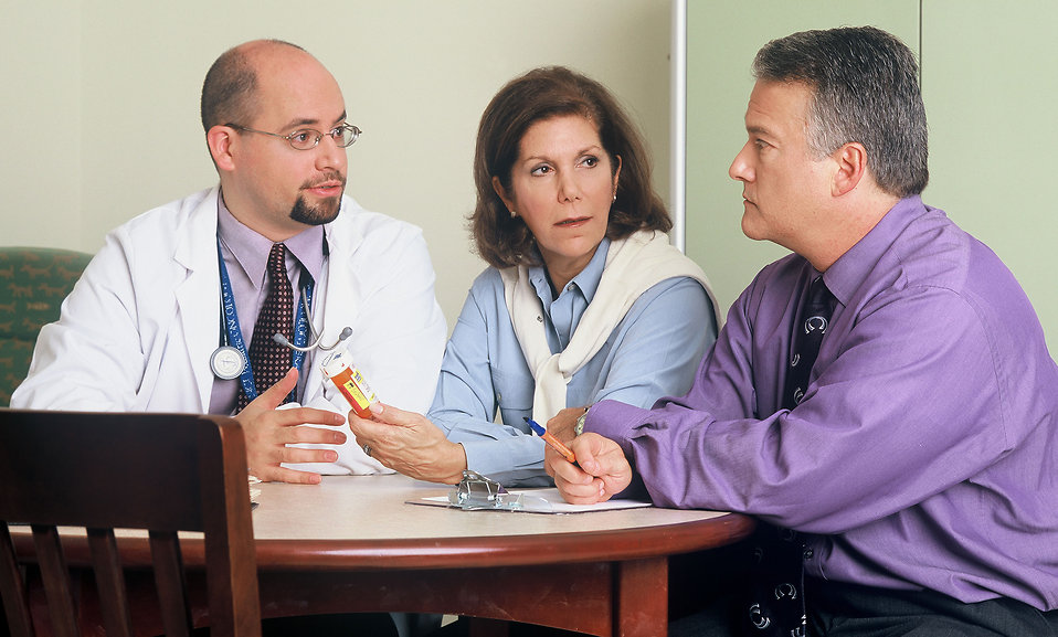 A doctor and couple talking : Free Stock Photo