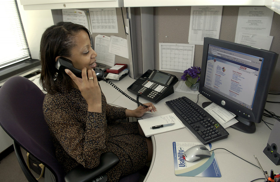 A Cancer Information Service (CIS) staffer (African-American female) answers the phone and provides assistance to a caller.