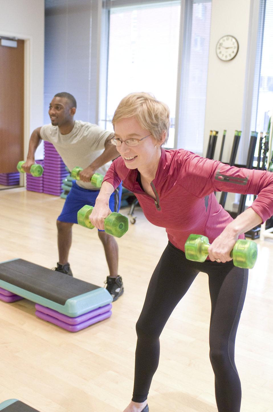 Men and women performing aerobic exercises : Free Stock Photo