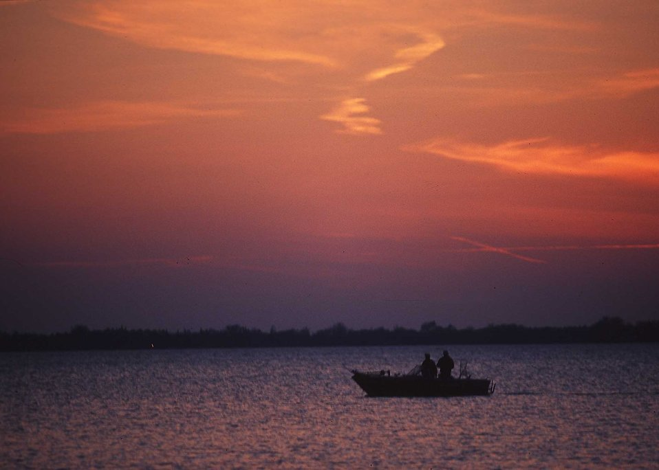 A fisherman in a boat on a lake : Free Stock Photo