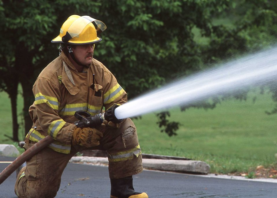 A Redings Mill, Missouri, firefighter sprays water pumped from a portable tank filled with water from a dry hydrant. Dry hydrants and portable tanks greatly improve fire fighting capabilities in rural areas.