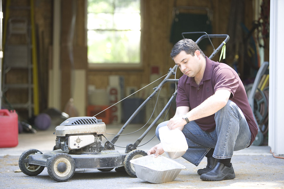 This man was in the process of changing his lawnmower\'s oil. .
