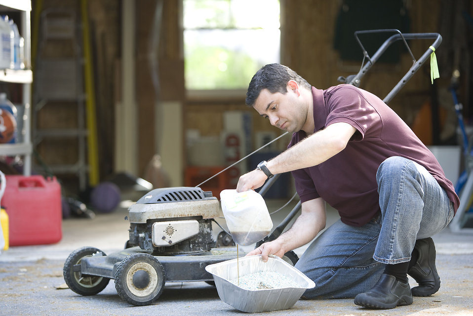 A man working on his lawnmower : Free Stock Photo