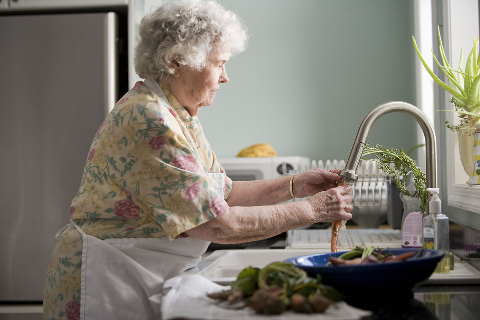 An elderly woman washing produce : Free Stock Photo