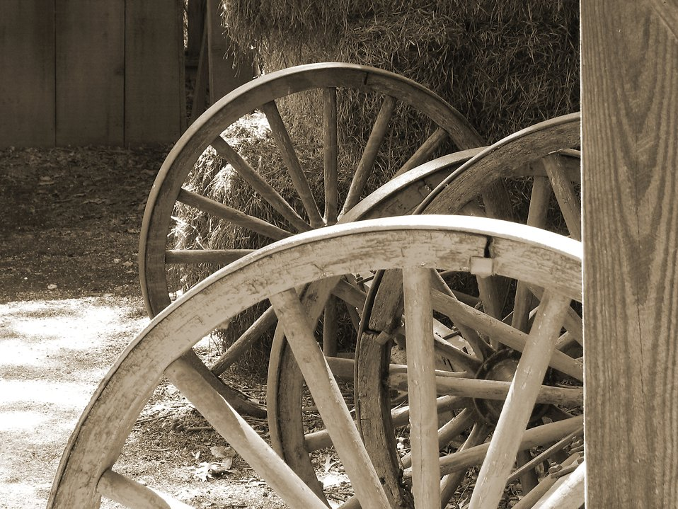 Black and white picture of wooden wheels and hay in a barn : Free Stock Photo