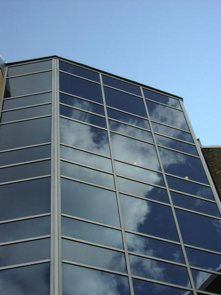 Sky reflecting off a glass building : Free Stock Photo