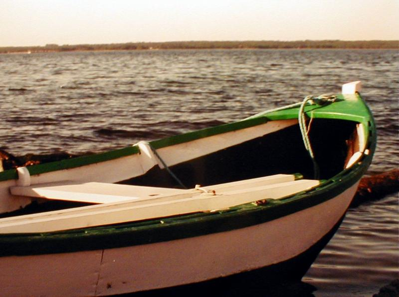 A small wooden boat on a lake : Free Stock Photo