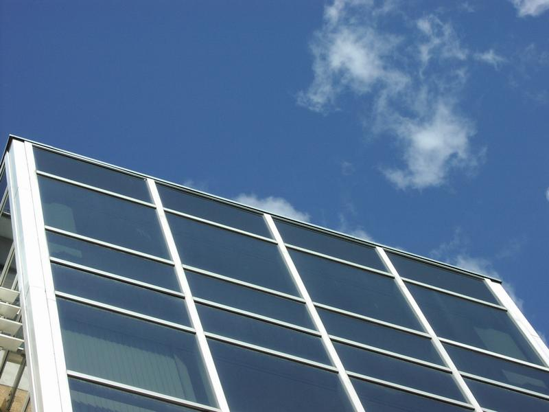 Closeup of modern glass building with blue sky : Free Stock Photo