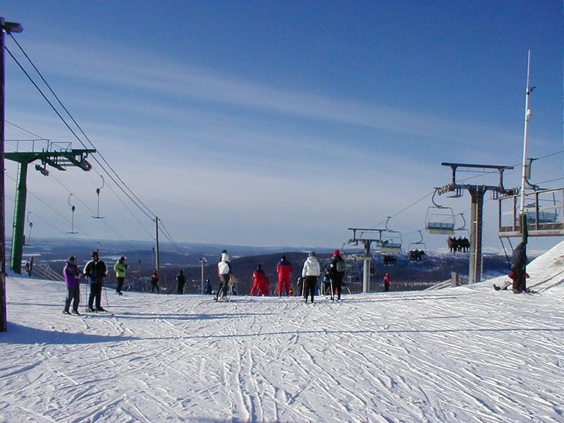 Skiers and chair lifts at the top of a mountain : Free Stock Photo