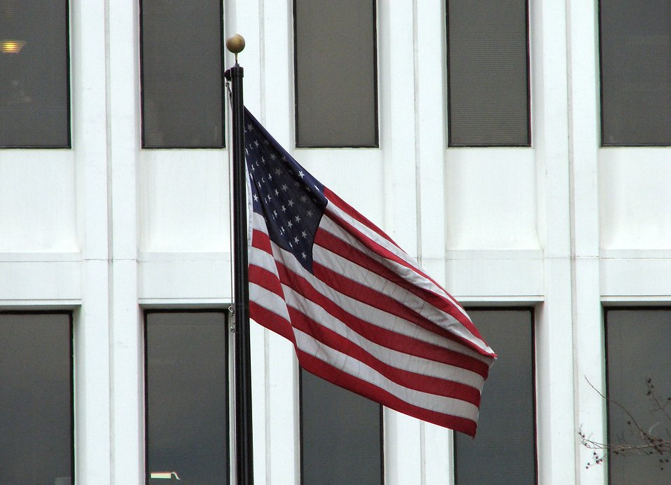 US flag in front of a white building : Free Stock Photo